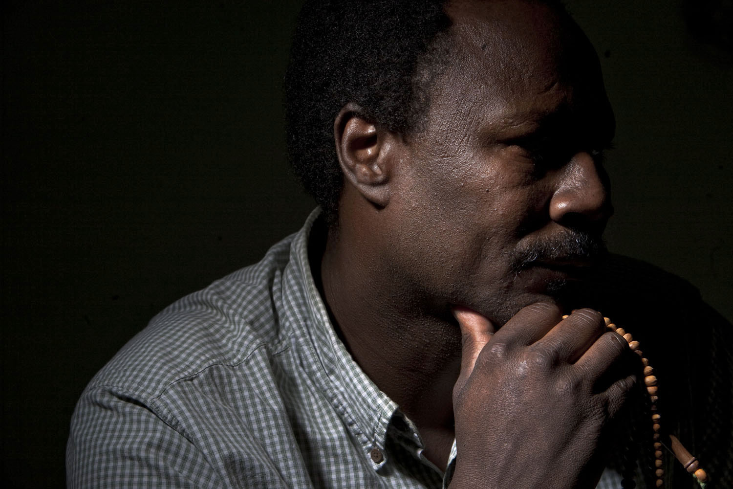 Gouma Mahamat holds religious sephaa beads in his Kensington apartment. The faint lines on his temple, received at age 2, identify him as a member of the Zaghawa tribe. Mr. Mahamat, a father of five, arrived in the United States in 1987. He considers himself the founder of the Brooklyn enclave of immigrants from Darfur, which now numbers over 300.
