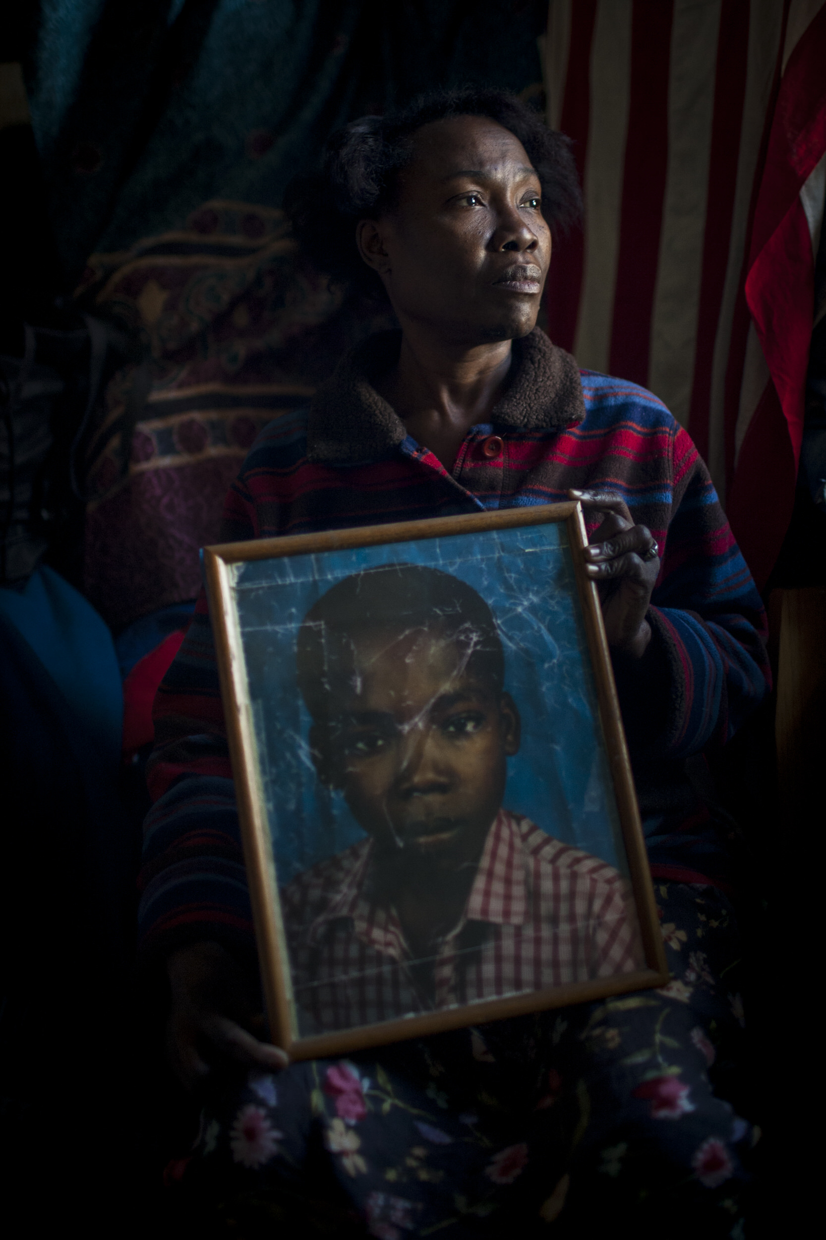 A Brooklyn woman holds a photo of her missing son, eventually found safe, after a devastating earthquake struck Haiti in 2010.