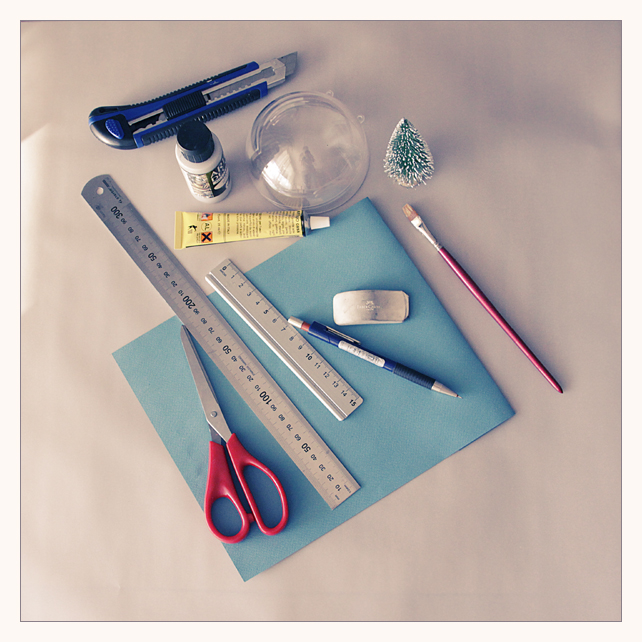 Для создания именного елочного шарика понадобится:    Пластмассовый ёлочный шарик из двух частей  Клей момент (или любой другой универсальный моментальный клей)  Клей для бумаги (я пользуюсь клеем UHU - он прозрачный и быстро схватывающий)  Лист цветной белой акварельной бумаги  Вата  Мини-ёлочка  Акриловая серебряная краска  Акриловая белая краска  Рассыпчатые серебряные блестки  Ножницы  Кисть плоская  Лента