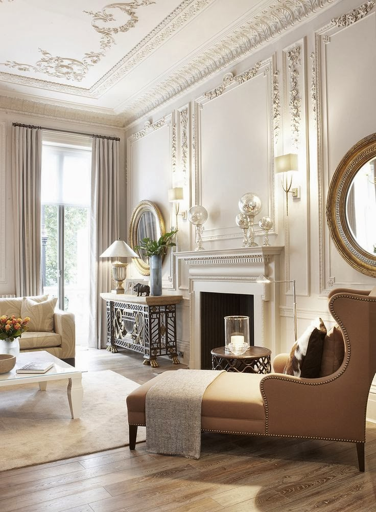 Главным концептуальным прёмом в оформлении этой гостиной стал контраст между богатой лепниной и лаконичными предметами обстановки в сочетании с простым паркетным полом. Обивка оттоманки однотонная, диван украшает укрупненный цветочный узор, а туалетный столик является ярким примером современной неоклассической мебели. Лепнина, не смотря на большую декоративность, окрашена в один цвет с потолком и стенами, что делает её менее заметной. Обратите внимание на карнизы, украшенные акантом – традиционным орнаментом античной Греции.