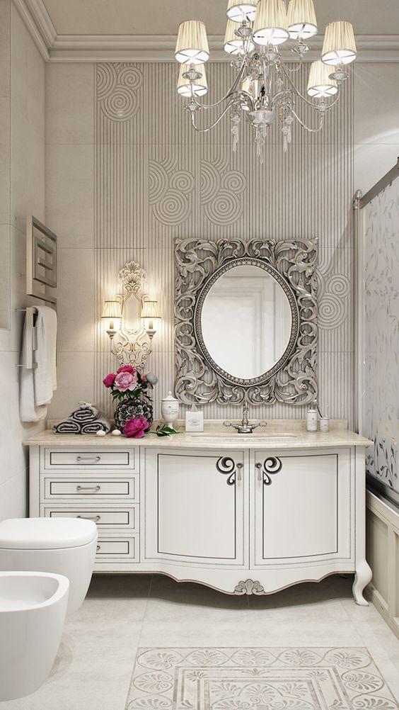 Прекрасный пример ванной комнаты в неоклассическом стиле: мебель классического силуэта окрашенная в белый матовый цвет, пол и тумбу с раковиной украшает традиционная для античной Греции пальмовая ветвь, зеркало в богатой резной раме серебряного цвета сочетается с хромированной люстрой классического силуэта.