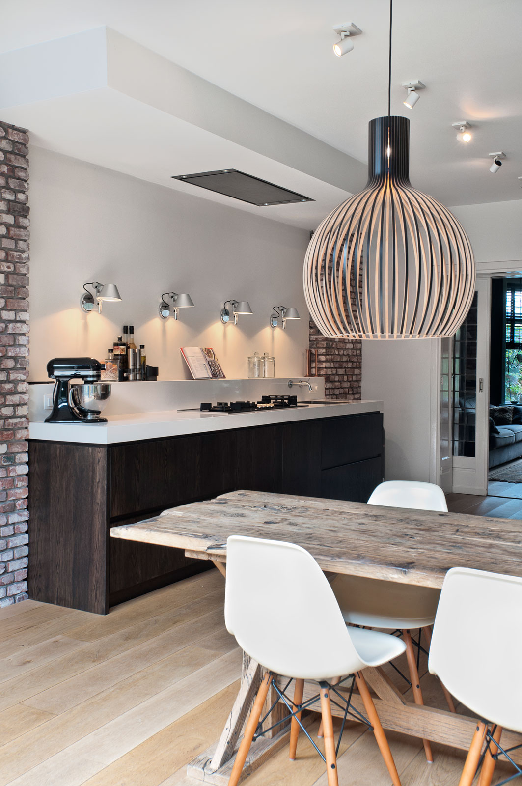 Пример продуманного многоуровневого освещения на кухне: направленное освещение рабочей поверхности посредством бра, большая декоративная люстра над обеденным столом, поворотные точечные потолочные светильники для основного освещения кухни. Источник: artemide.com