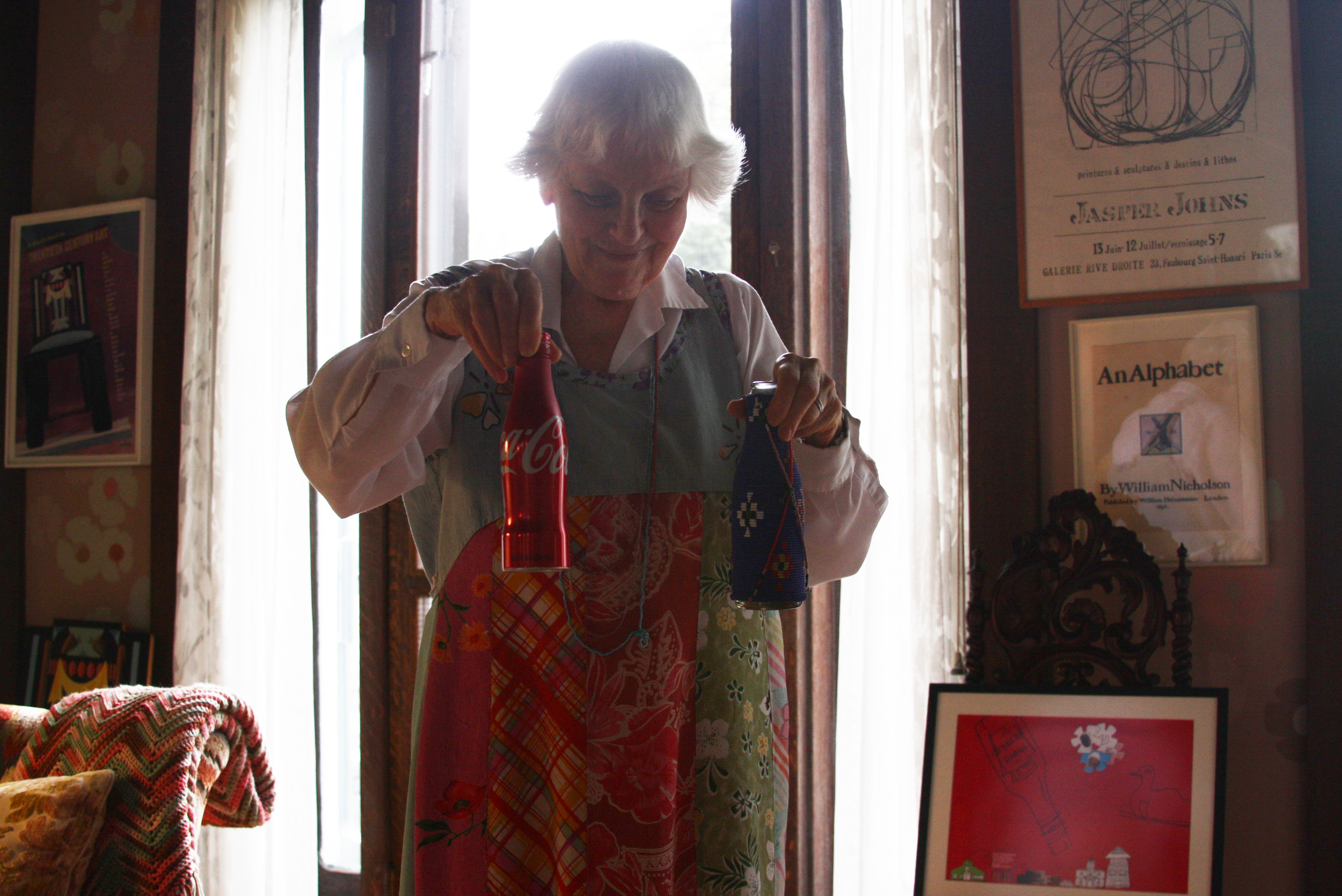 Denise Scott Brown showing Coca-Cola bottle and a handmade bottle from Africa