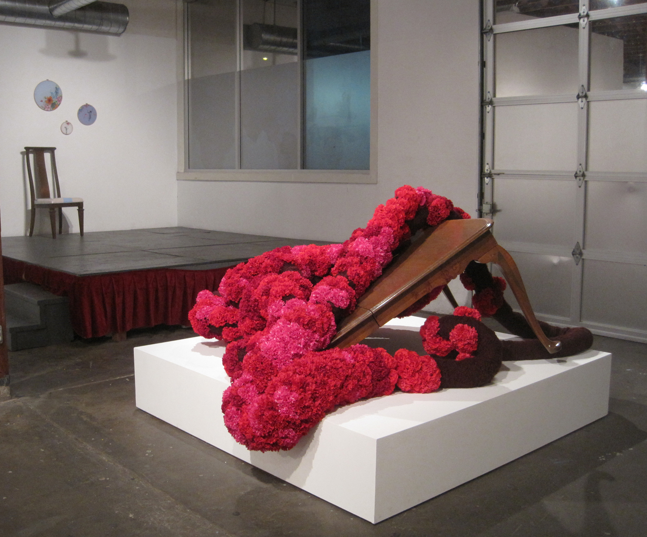 The Dreaming,  yarn, silk carnations, wooden table. dimensions variable, 2012.