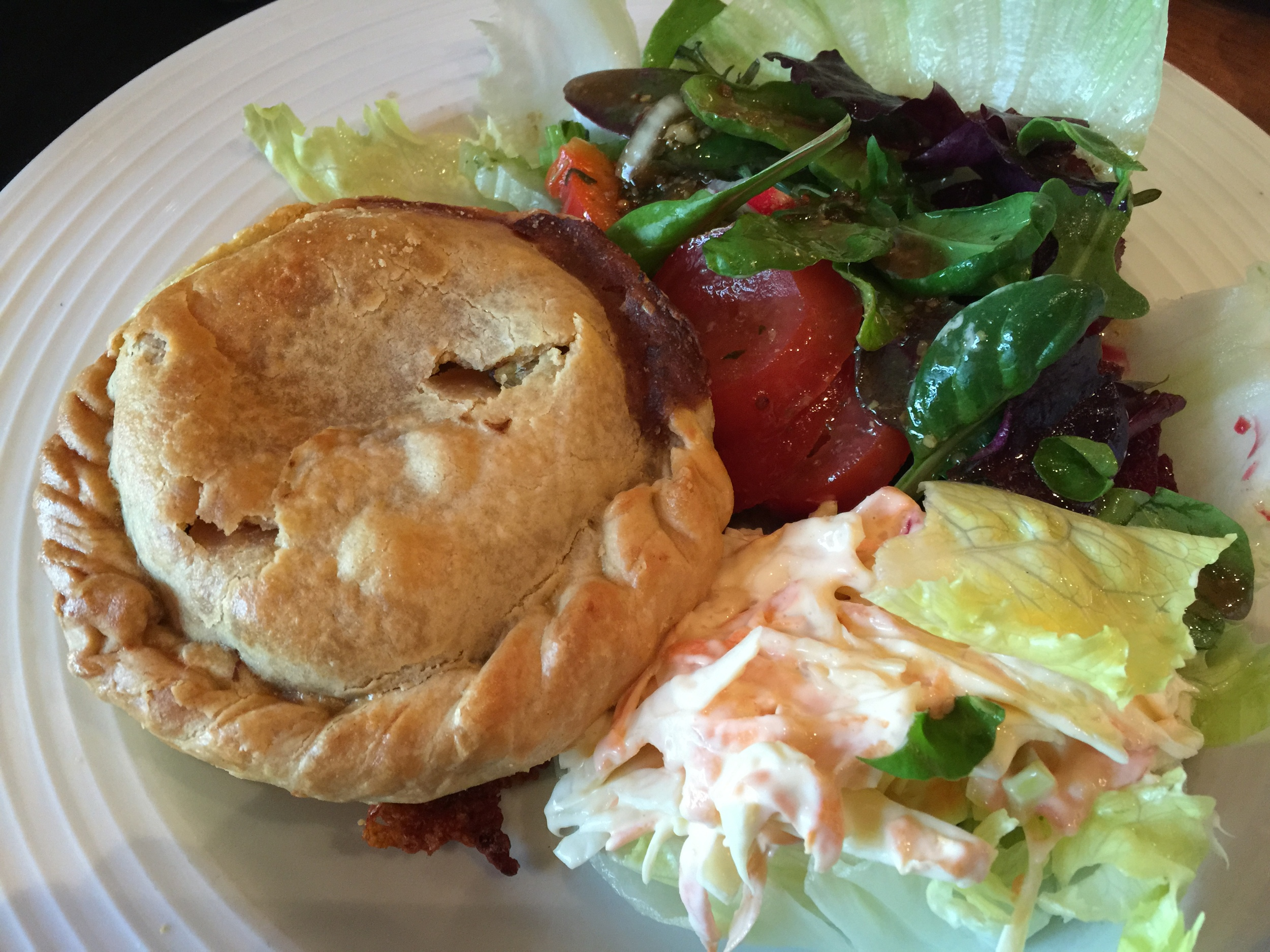 Some English Pub fare. A scrumptious meat pie with a cole slaw and fresh greens. Delightful fare and nothing eases the pain better than good food and good drink!
