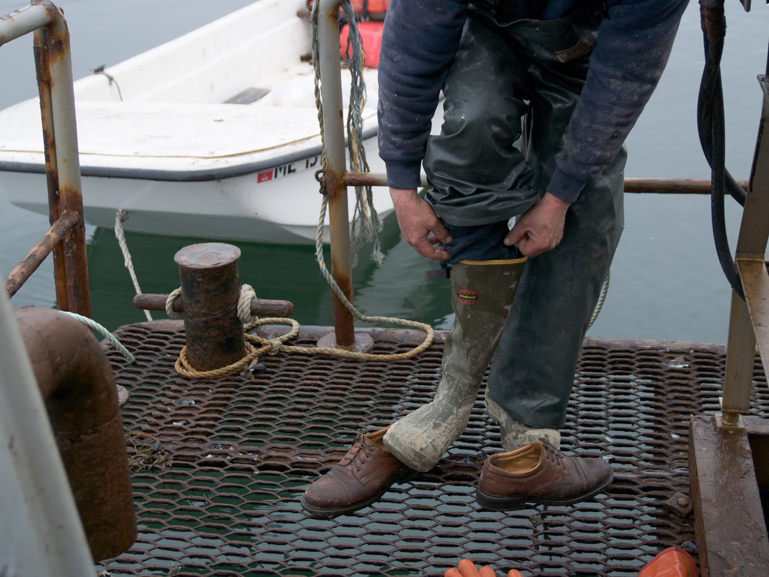 (04/04/09) Cater Newell pulls on a pair of boots. Rubber overalls and rubber boots are needed before getting to work on the barge. The job is a messy one and the crew have have to be prepared to work in all kinds of weather. In rough weather, waves wash over the deck of the boat, some- times spilling the mussels over the side and dur- ing the winter it's not unusual to spend the first hour of the day shovelling snow off the deck.