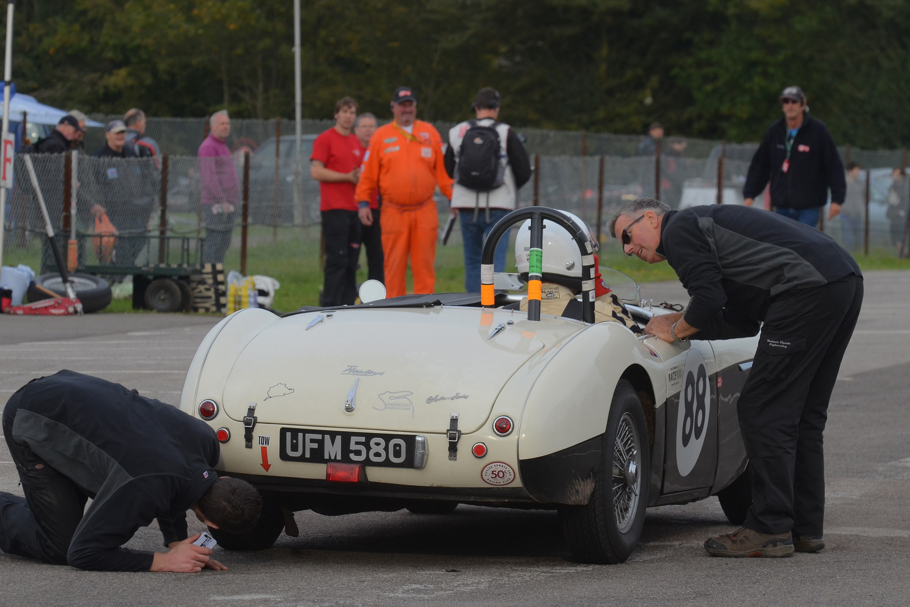 FISCAR hospitality supplier and sponsor, Paul Woolmer (Woolmer Classic restoration) ensures that all is well with Jeremy Holden in his recently acquired Austin Healey.                                                       Photo - Ollie Read