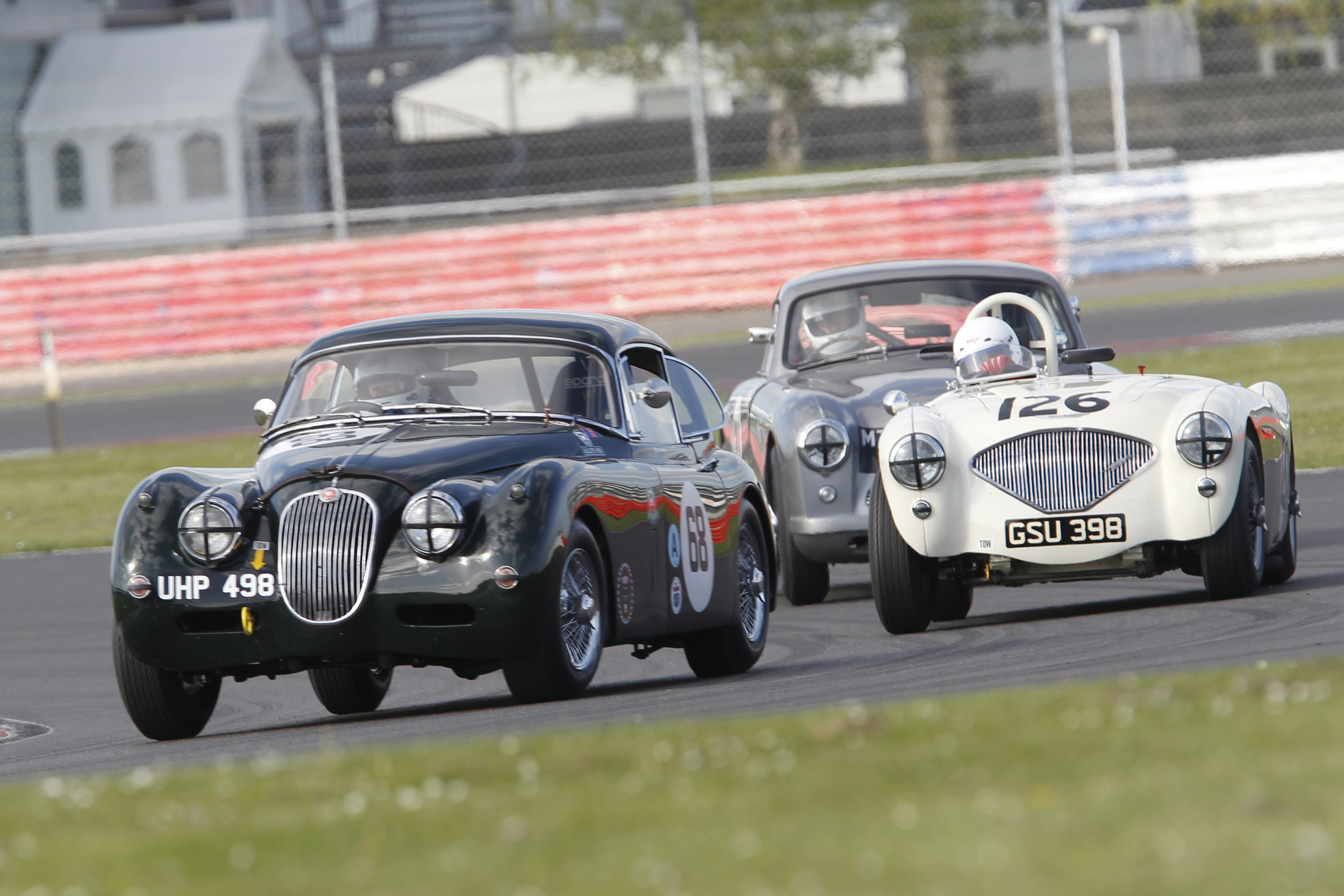 Classic 1950s Marques battle it out on the Silverstone GP Circuit. Marc Gordon (XK150), Nigel Grice (Austin Healey 100) and Tim Stamper (Aston Martin DB2/4) Photo - Mick Wa;lker