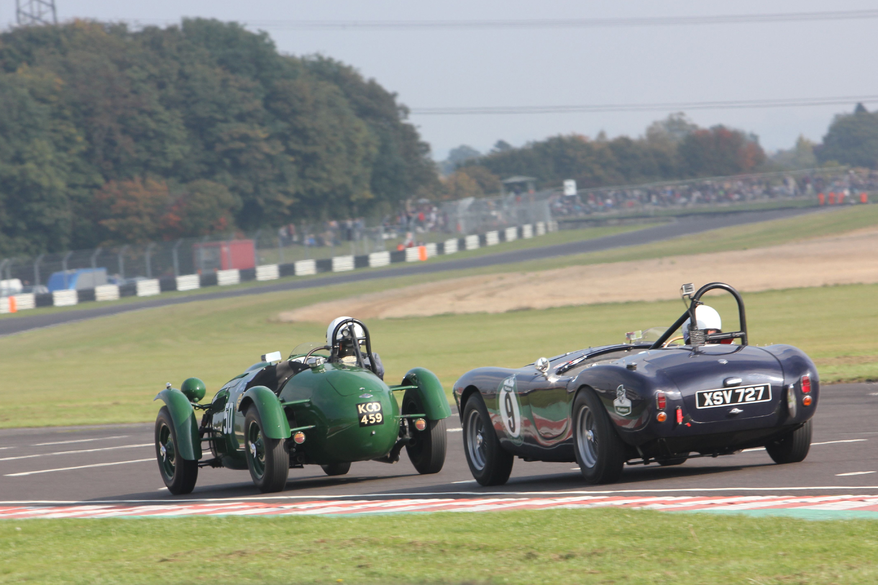 Martin Hunt (Frazer Nash Le Mans Replica) and Ted Murray (AC Ace), lying at this stage 8th and 9th head down the pit straight towards Folly which appears a much more accentuated corner from this angle than it does from most spectator viewpoints and is probably the fastest part of the circuit. The track section above the drivers heads is called appropriately Avon Rise followed by the gentle left hander into the difficult right hander, called Quarry.  Photo- Pat Arculus, Tripos Media