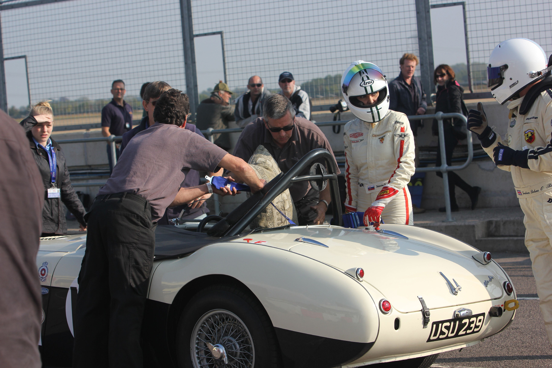 Katarina Kyvlova listens to some sage words from car owner Graham Robson before she replaces him in the hot seat  of the Austin Healey 100M. The 'Cool Dude' in shades is Paul Woolmer of Woolmer Classic Engineering, our sponsor and provider of excellent hospitality unit throughout the season.  Photo - Pat Arculus, Tripos Media