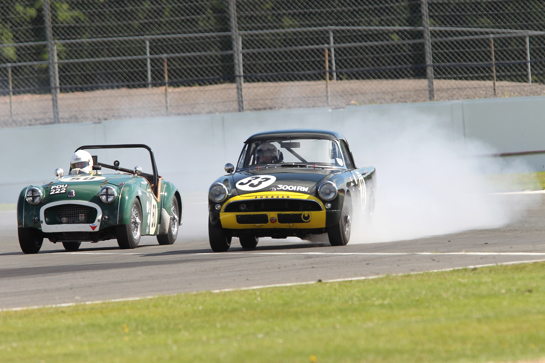 A burst oil pressure gauge pipe brought the Sunbeam Alpine Le Mans practice to a rapid halt and some interesting moments for fellow competitors. Mark Hoble on the inside qualified his TR2, 15th. Photo - Mick Walker