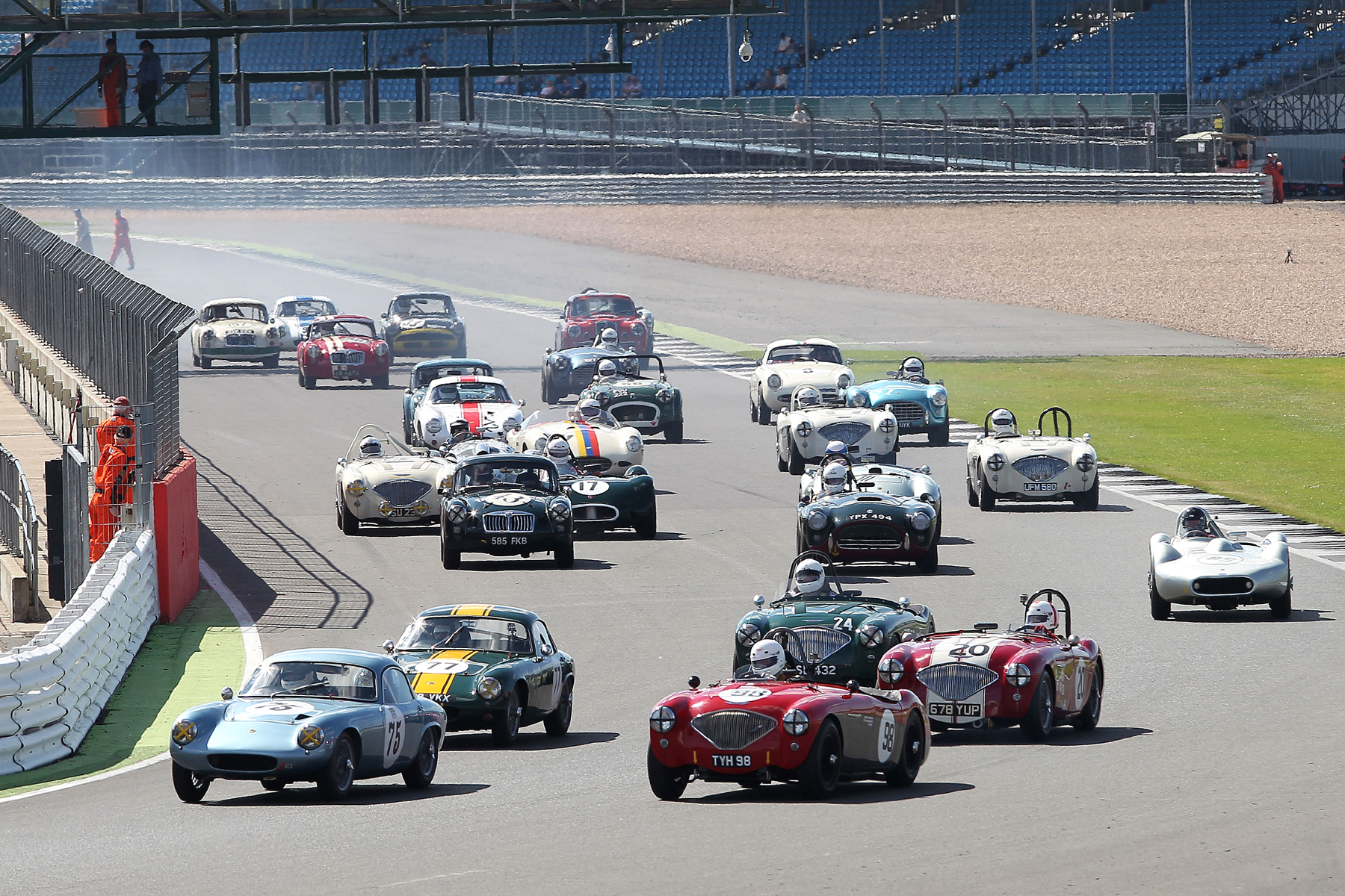 The Lotus Elites of Robin Ellis and Mike Freeman take advantage of the inside line to make places . All the cars but one are in picture here with the exception being Terry Bryant's MGA hugging the pitwall. Photo - Mick Walker