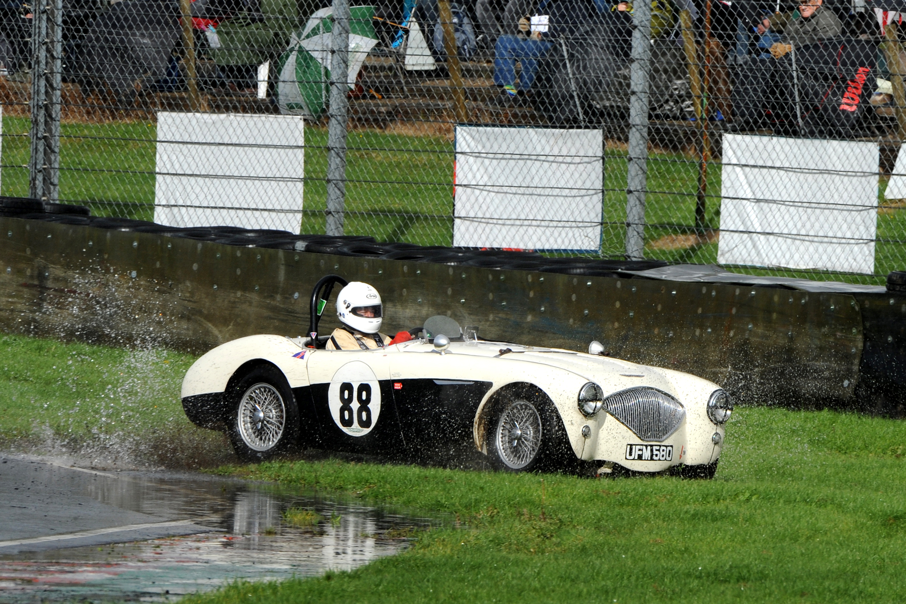 Into Quarry, braking too late, Jeremy Holden sensibly lets his Austin Healey run onto the grass. He returned safely to the track. I think this may be on his out lap following his pit stop when the brakes had cooled.                                Photo Jeff Bloxham