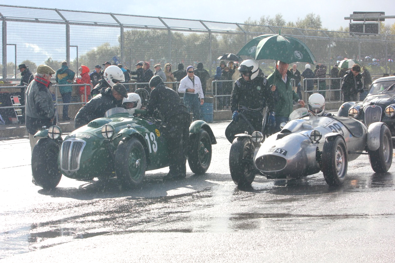 The sun is trying to make its presence felt but it is still raining as a pair of cycle wings take their pit stops. On the left, Martin Hunt gets strapped into his Frazer Nash Le Mans Replica whilst Patrick Blakeney-Edwards starts to remove his helmet. On the right, Peter Campbell, having removed himself and seat from the Wingfield Bristol Special also looks over at the FN whilst co- pilot Andrew Mitchell ensures that everything inside the cock pit is in order!                                                                     Photo - Pat Arculus, Tripos Media