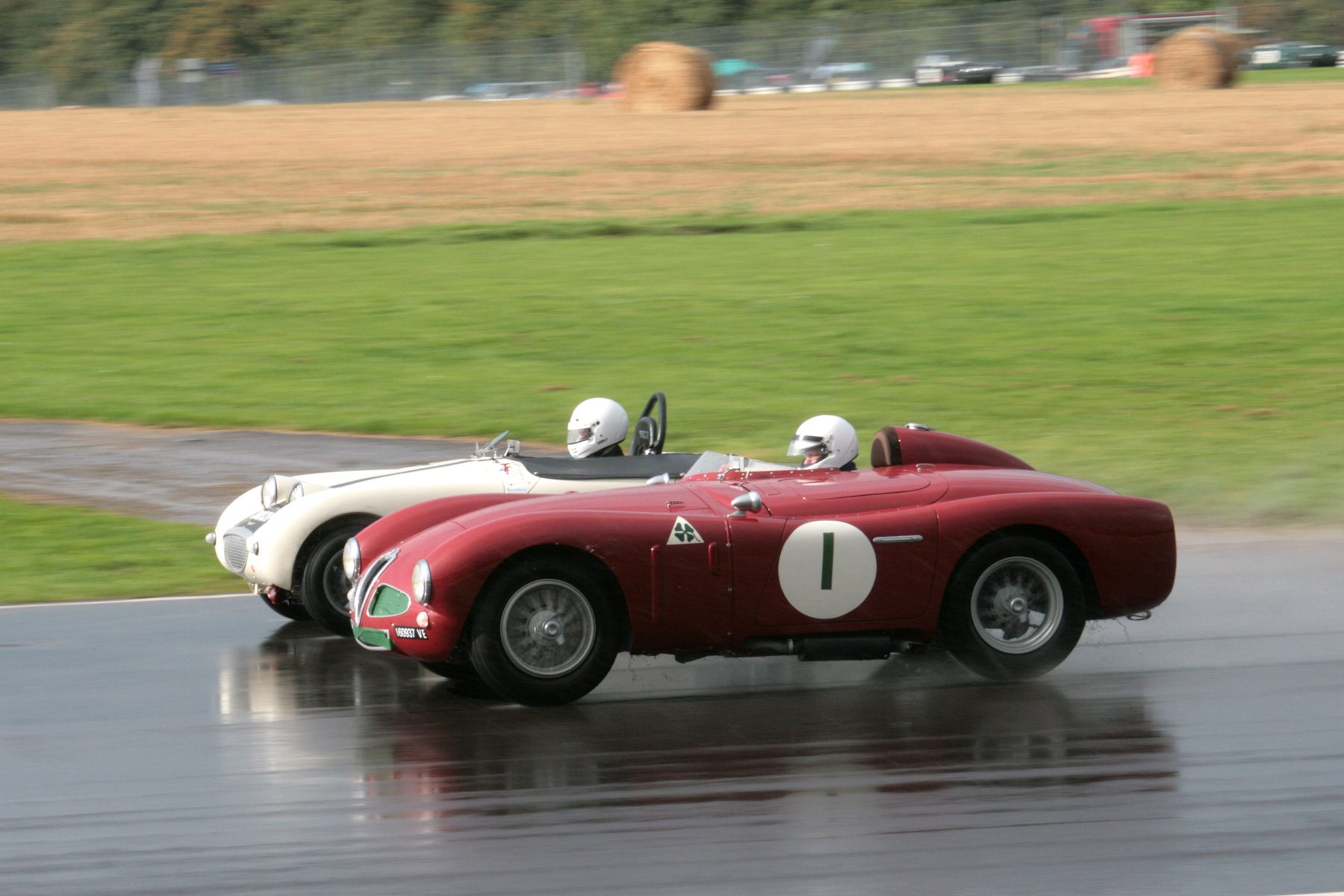 Neil Cameron in the little Frogeye Sprite is inevitably dwarfed by the Alfa Romeo Disco Volante of Chris Mann. Conditions were so cool that Chris had blanked off half the intake area with green masking tape.                Phot - John Turner