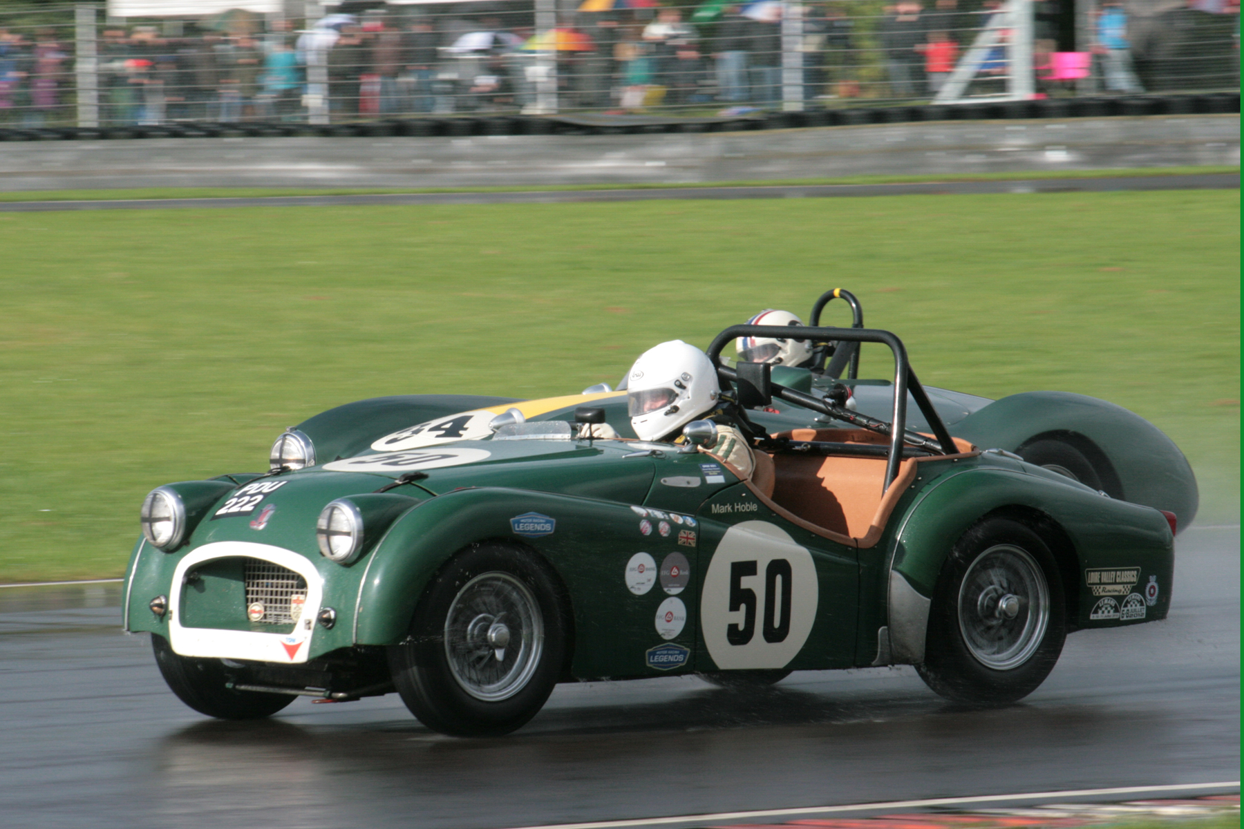 Mark Hoble in his TR2 being lapped by the winning Aston, but Mark won his race long battle with Paul Ziller in the other TR2 by just 2.5 seconds after 30 minutes of racing, winning his class in the process.                                                 Photo - John Turner
