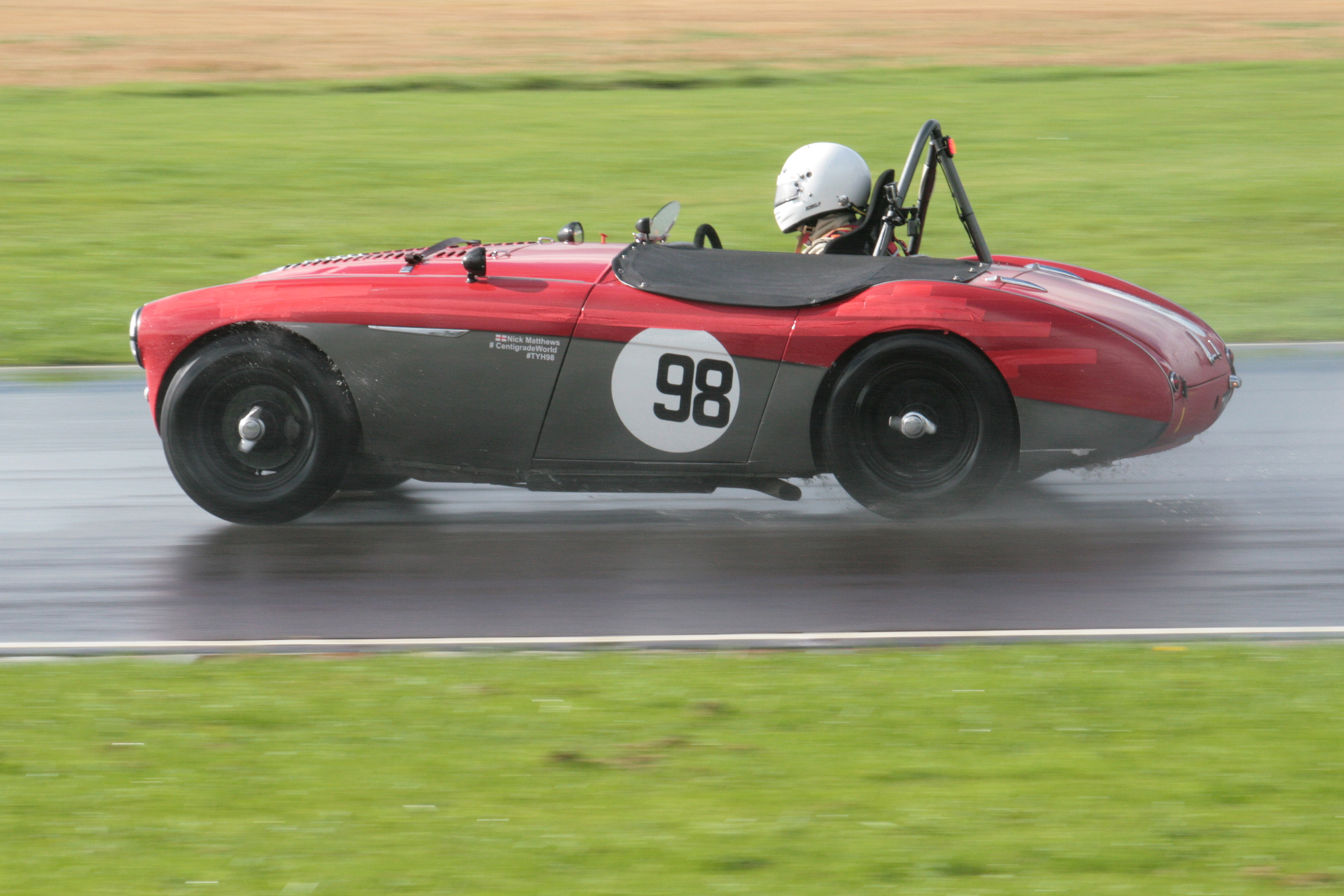 Nick Matthews finished 2nd overall despite his best attempts to avoid the race when during qualifying for the Healey race he overcooked it going into Camp and slid the car along the barriers - fortunately only cosmetic damage ensued - note the strips of red tape along the side.  Photo - John Turner