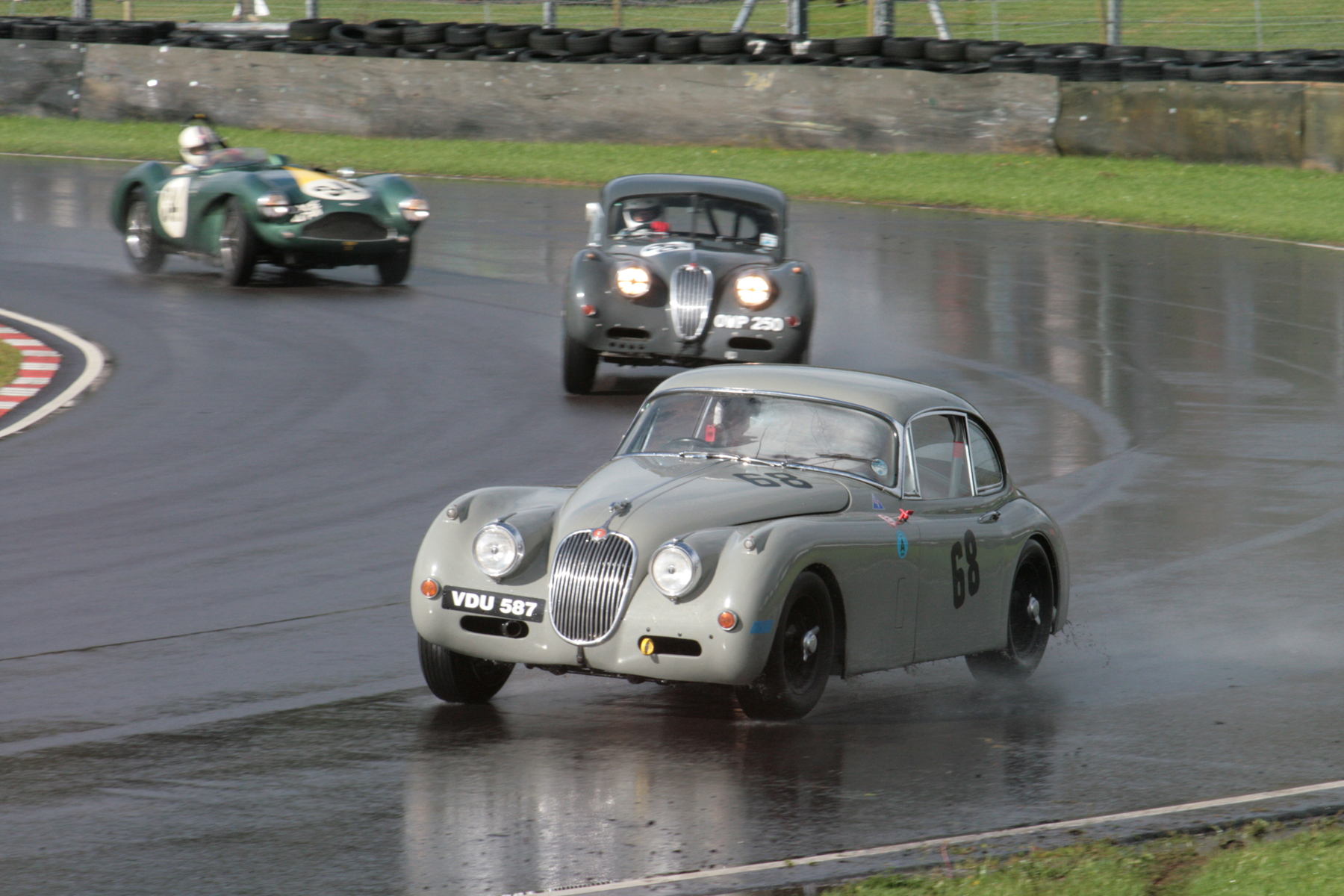 Paul de Havilland takes a wide line out of Quarry in his Jaguar XK150 whilst looming large behind is the lead battle .    Photo - John Turner