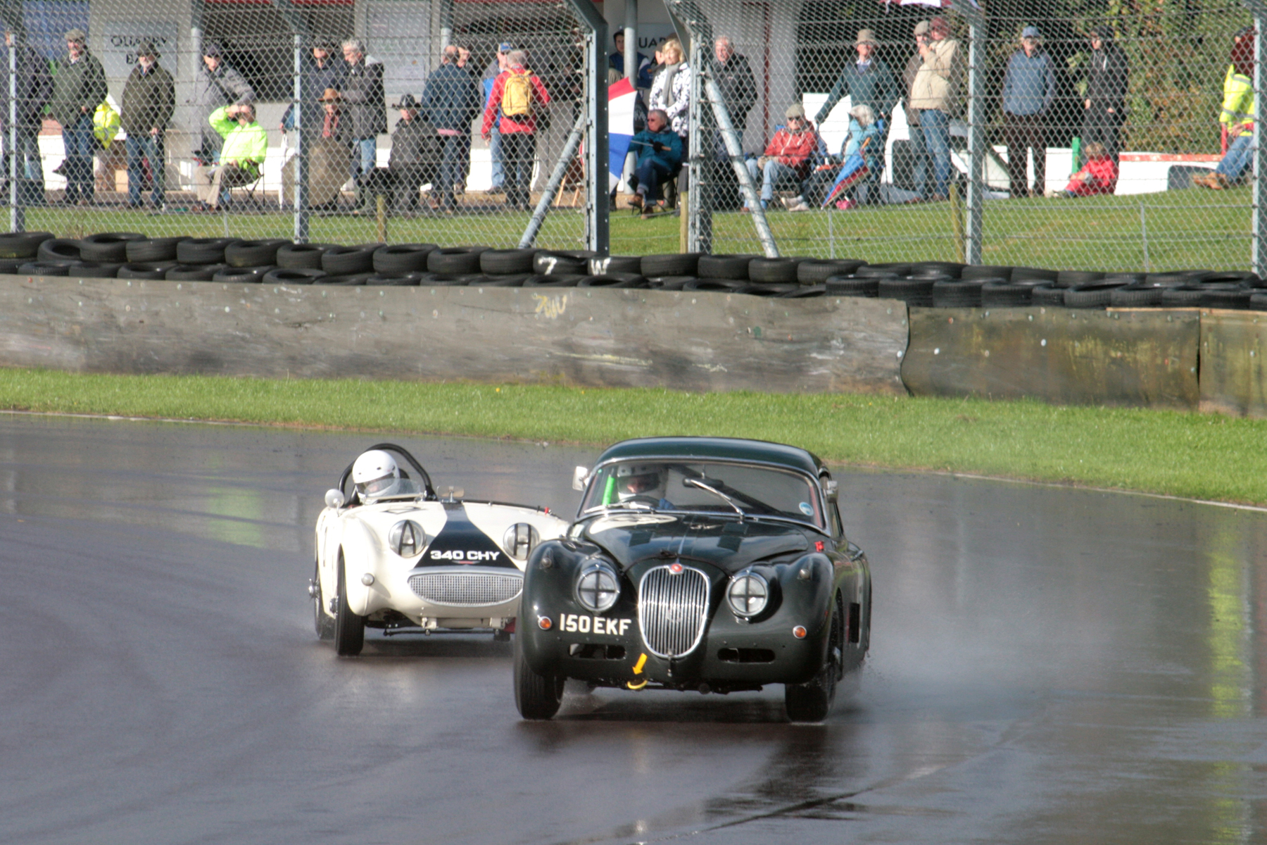 Claire Keith-Lucas in her Jaguar XK150 and Neil Cameron.  Note all the spectators braving the elements.          Photo - John Turner