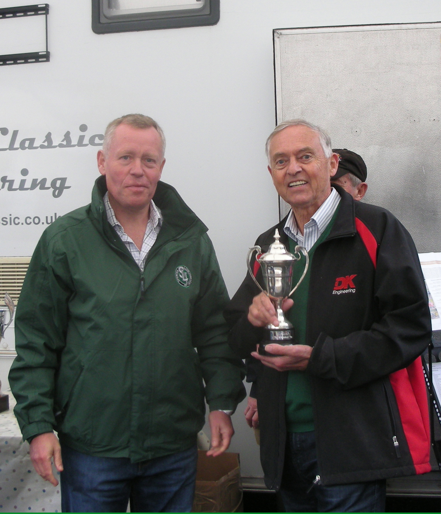 David Cottingham holds the Whitehead Cup, just presented to him by Miles Toulson-Clarke, owner of Spencer Lane-Jones Ltd, who sponsored our Castle Combe race for the second year running. They stand in front of the Woolmer Classic Engineering unit which has again provided our members with splendid hospitality all season. Photo - Pat Arculus, Tripos Media