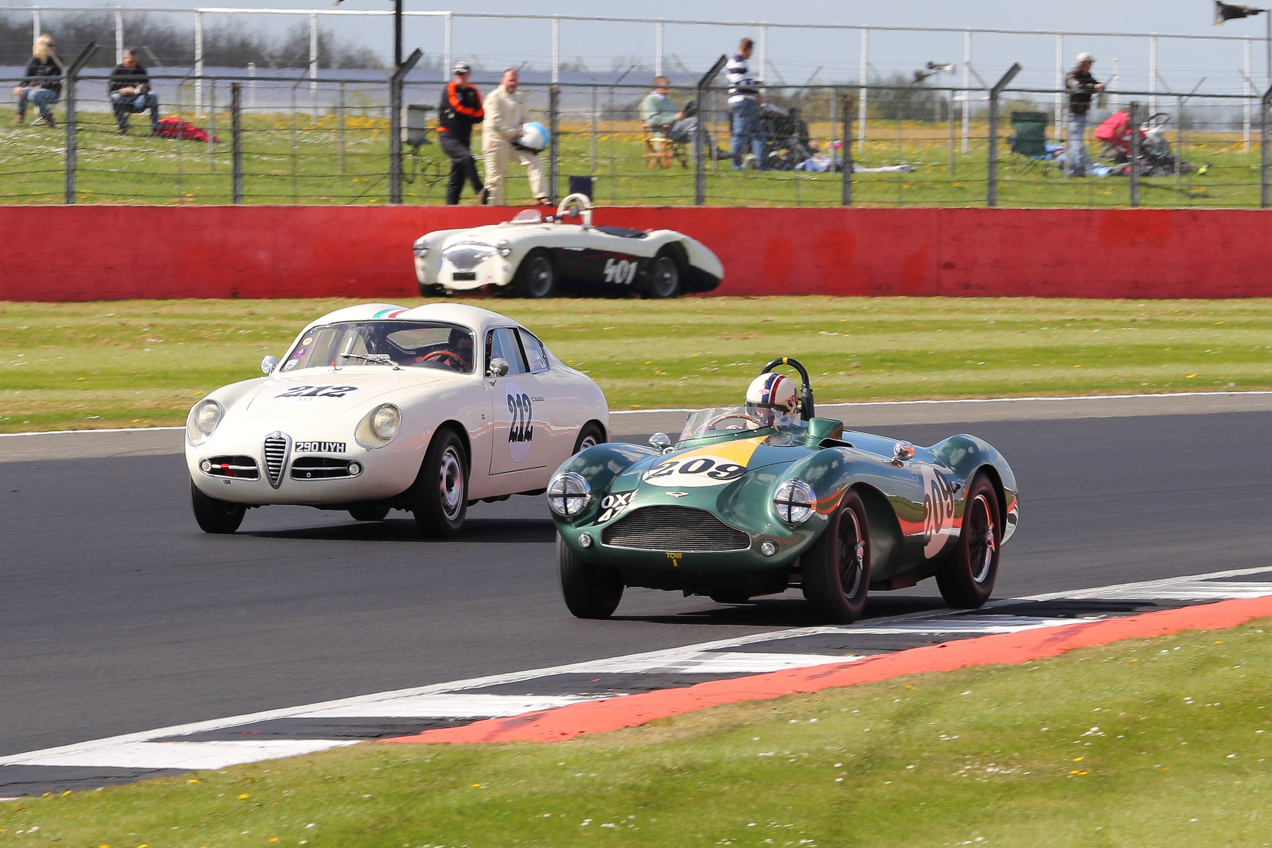 Steve BB takes the Aston passed Brian Arculus in the Alfa whilst Jason Harris looks on above his parked up Austin Healey.     Photo - Richard Styles