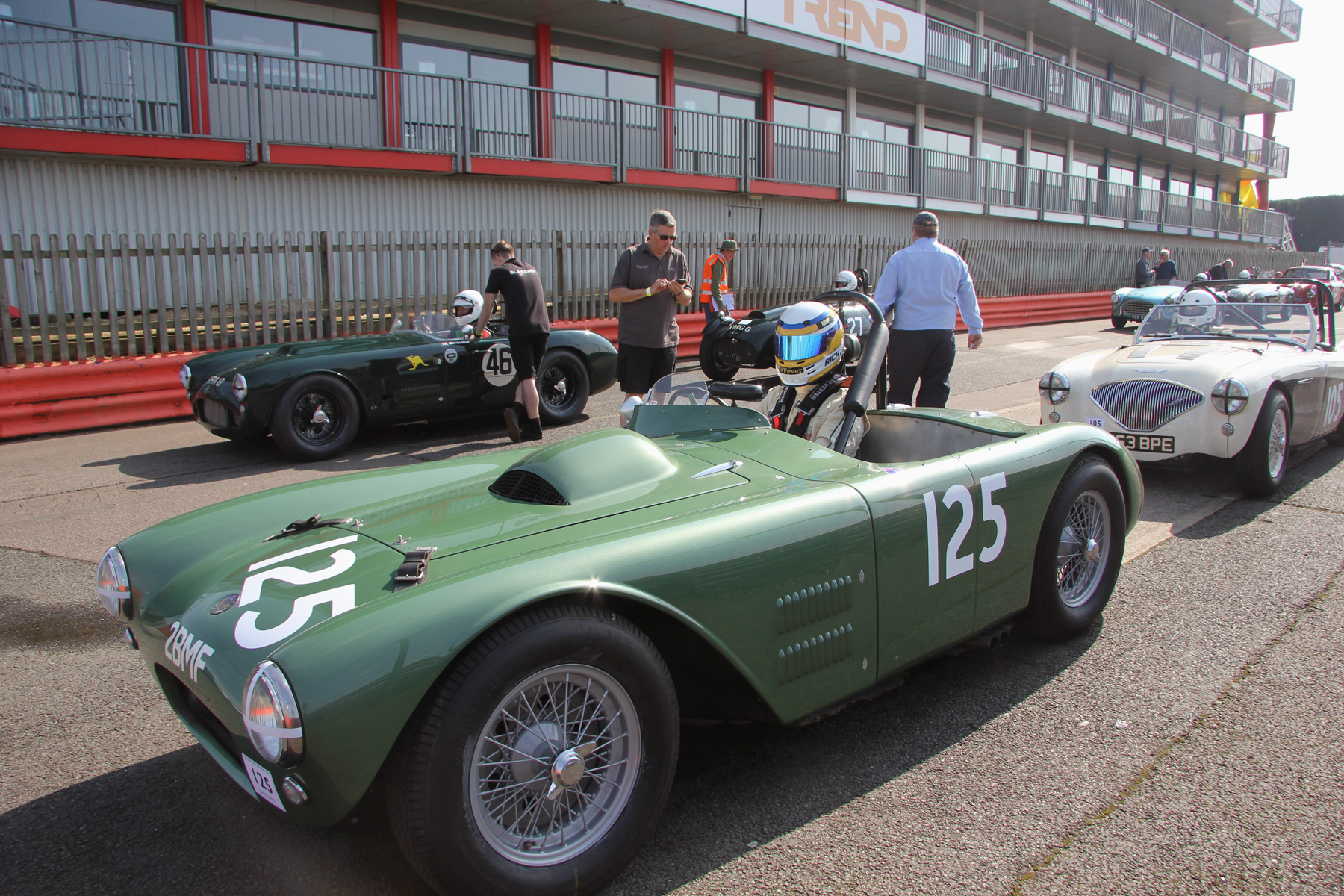 Richard Woolmer awaits the start of practice in Matthew Collings HWM Cadillac V8. Matthew is in the Austin Healey 100M  lined up behind and at the head of the other queue is Martin Hunt's  HWM Jaguar. Great to see two of 60+ year old products of Walton still gracing our tracks.  Photo - Pat Arculus, Tripos Media