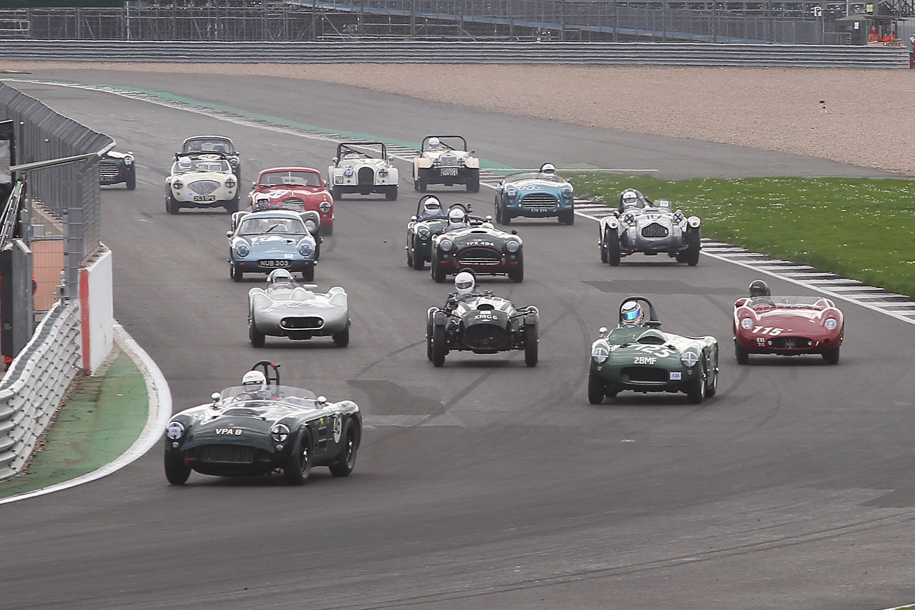 Great start by Martin Hunt took his HWM into the lead, whilst poleman, Richard Wilson, in his Maserati 250S has made a poor one and dropped to 3rd behind Richard Woolmer in the  HWM Cadillac. Level with the Maserati is Martyn Corfield in the Frazer Nash LMR who has beaten Stephen Bond to the punch off the line. Please note the two white Morgans towards the back. Both Plus 4 models, Mark Shears Flat rad car is from 1952  whereas Alan House's is  from 1959.                                                                                                          Photo - Mick Walker