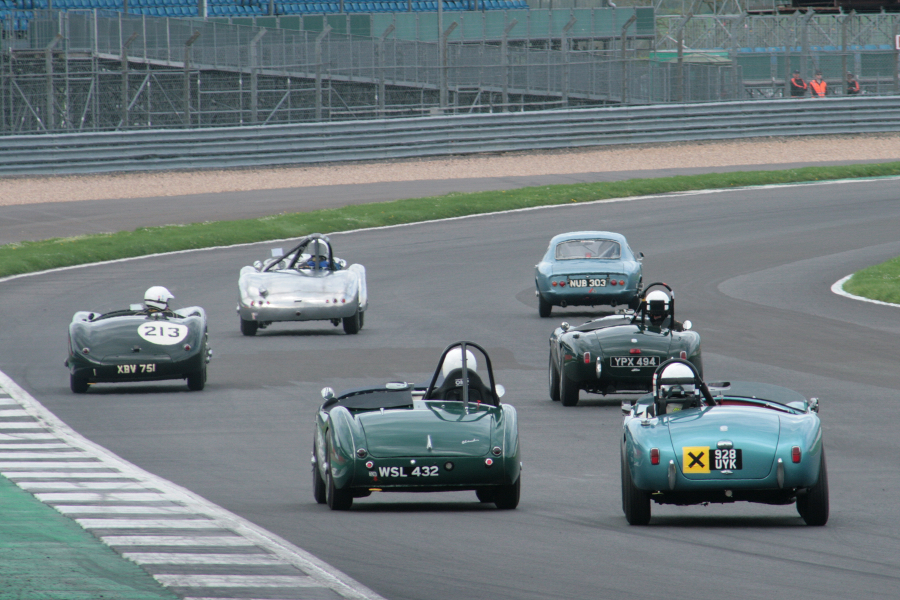 The Lotus emerges ahead of the Allard albeit briefly whilst Dave Brazell  in the Jaguar C -Type looks across at Tim Pearce in the AC Ace and Jim Campbell and David Cottingham have a grandstand view.   At the end of lap 2 the 6 cars were even closer but the Elite just held sway at the line, see text.                                       Photo - John  Turner
