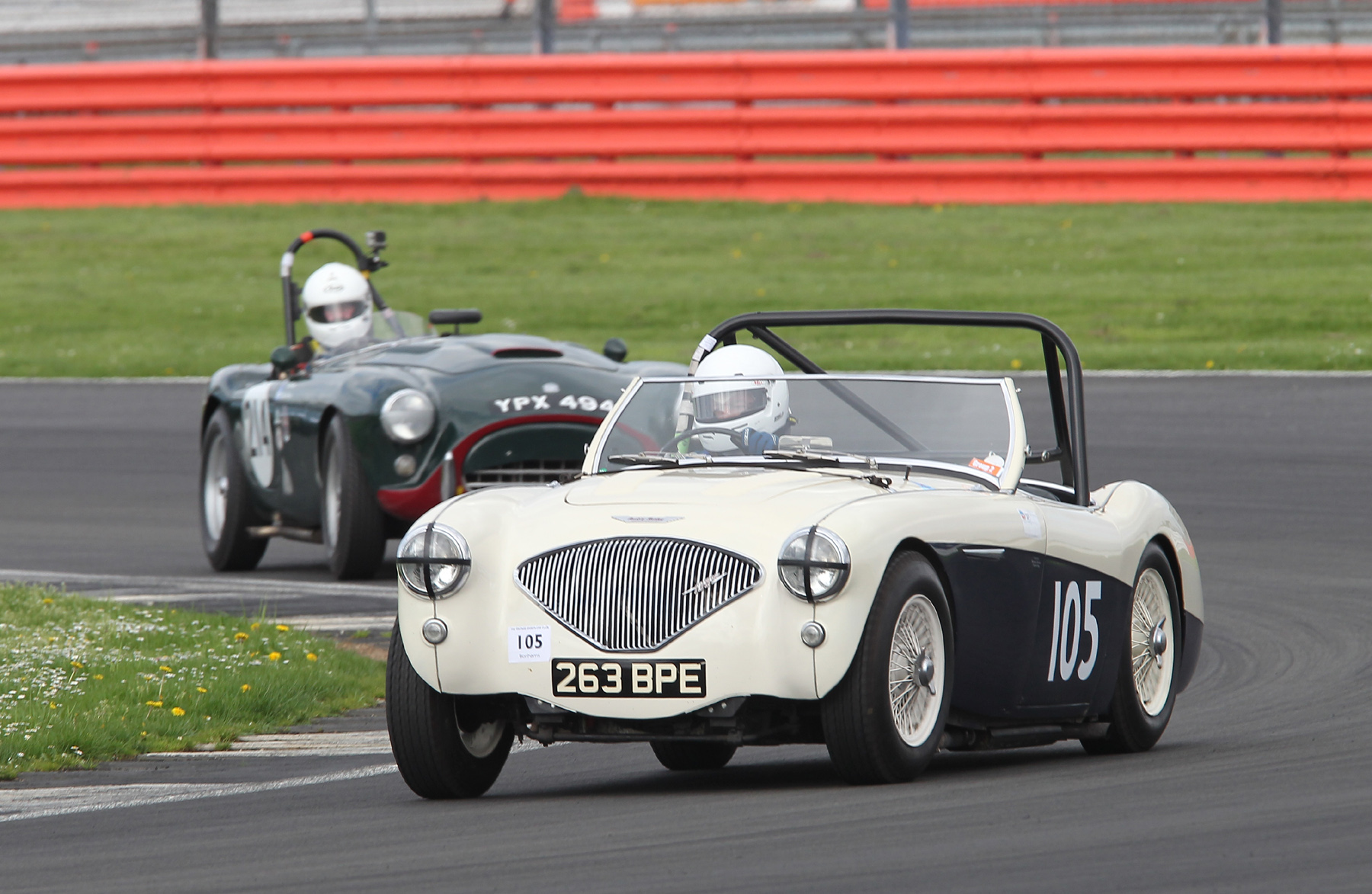 Matthew Collings presses on in his very standard Austin Healey 100M but is about to be lapped by Tim Pearce inn his AC Ace Bristol    Photo - Mick Walker