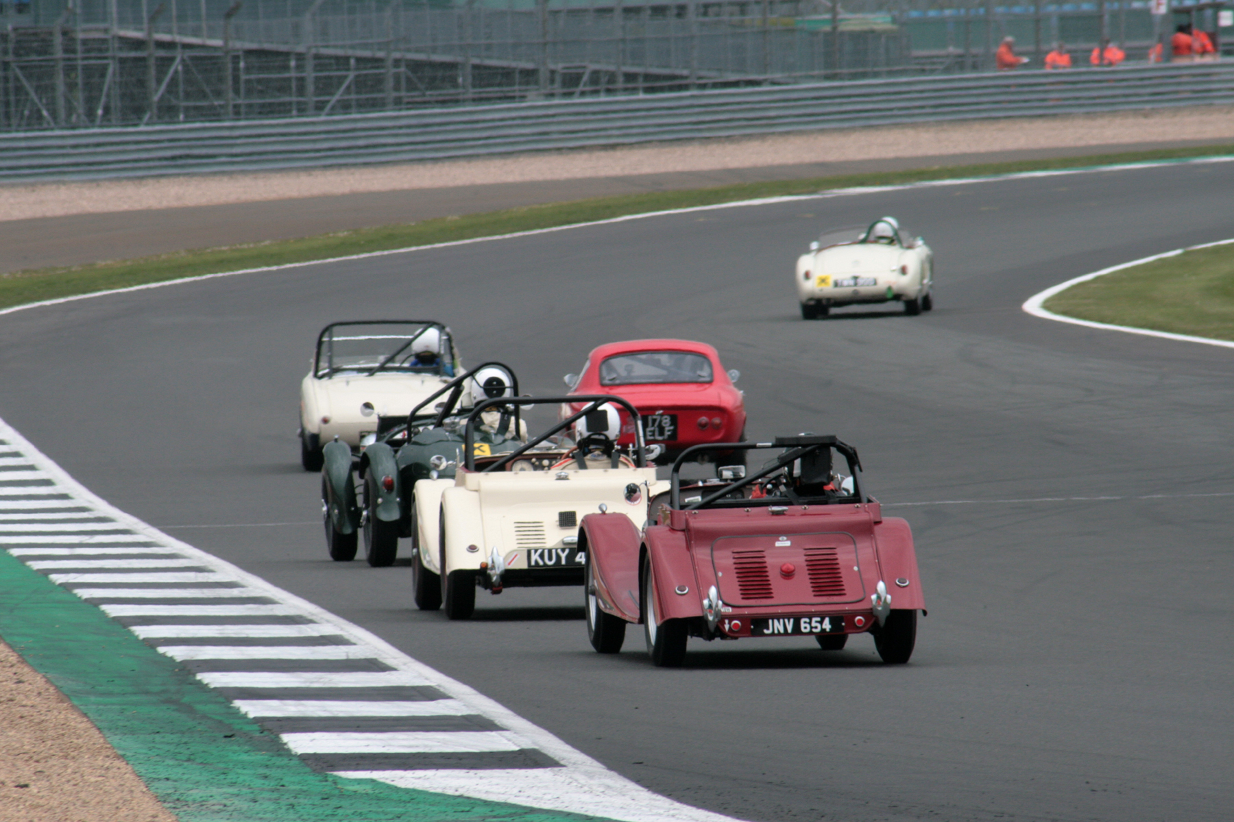 The battling at the back was equally close. As the MGA Twin Cam of newcomer Nick Burnside pulls clear in 23rd place, Dougal Cawley, recovering from his poor start in the Elite, took several places and is seen here challenging the Austin Healey of Matthew Collings. Behind them are the Frazer Nash LMR of Thomas Ward and the dicing Morgans of Mark Shears and Leigh Sebba. Only the Jowett Jupiter of Harry Naerger is yet to come through to complete the first l.ap. Photo - John Turner