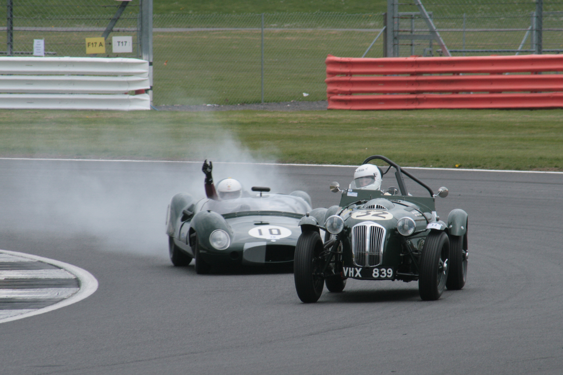 Thomas Ward exiting Luffield in his Frazer Nash Le Mans Replica, not quite lapped by the Cooper Monaco driven by Andrew Smith who is indicating his intention to pit and retire. Photo - John Turner