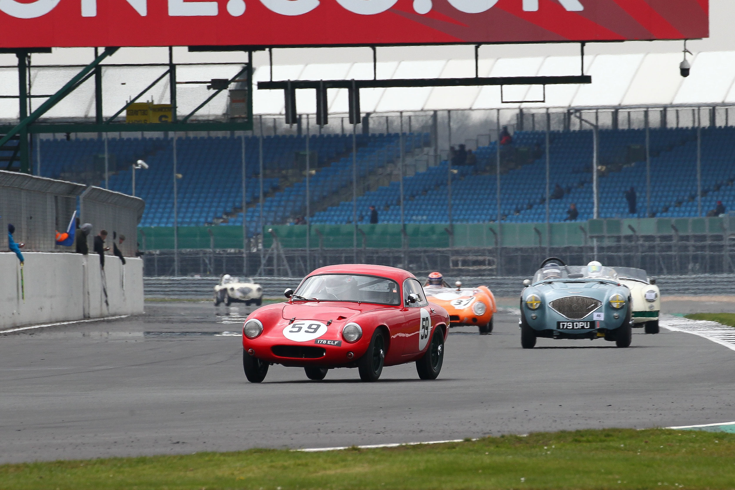 Dougal Cawley (Lotus Elite) Leads Robert Clarke (Austin Healey 100) and Nick Burnside (MGA Twin Cam). They are all about to be lapped by the leader, Philip Walker in the orange Lotus 15. In the background, is Matthew Collings in his Austin Healey 100M. Photo - Richard Styles