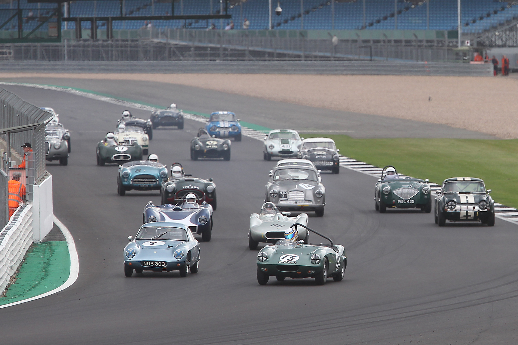 At the start, Richard Woolmer just has the nose of the Courier ahead of the Lotus Elite of Brian Arculus. Tucked in behind are Stephen Bond and Richard Tyzack with John Andon on the outside in his Triumph TR4, the first of the Pre 64 CMMC cars. Note the great start by Tim Stamper in Richard Bell's Aston Martin DB2/4, already up to 6th from 10th on the grid.  Photo - Mick Walker