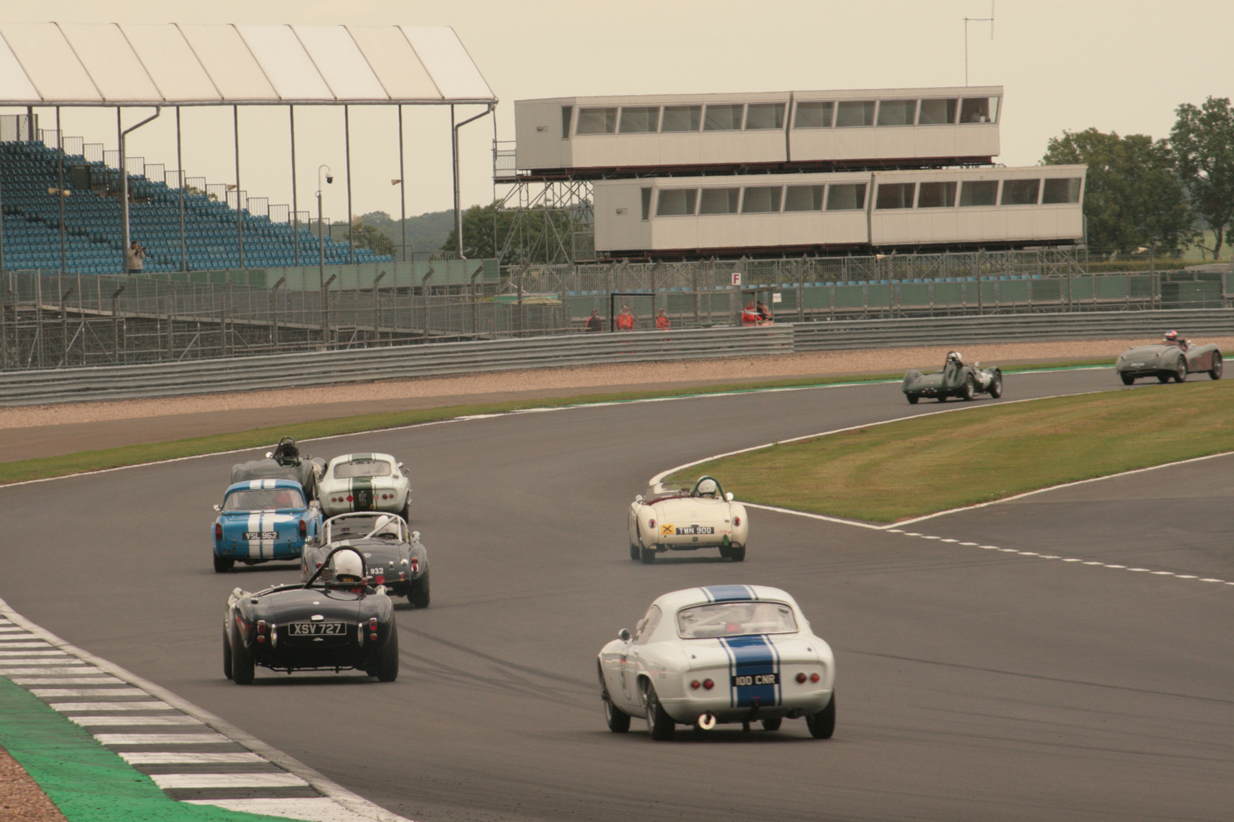 Close racing at the back, as they pour through Woodcote for the first time. Although last here, Nick Atkins had gained a place at the expense of the AC Ace by the time they entered the second lap.  Photo - John Turner
