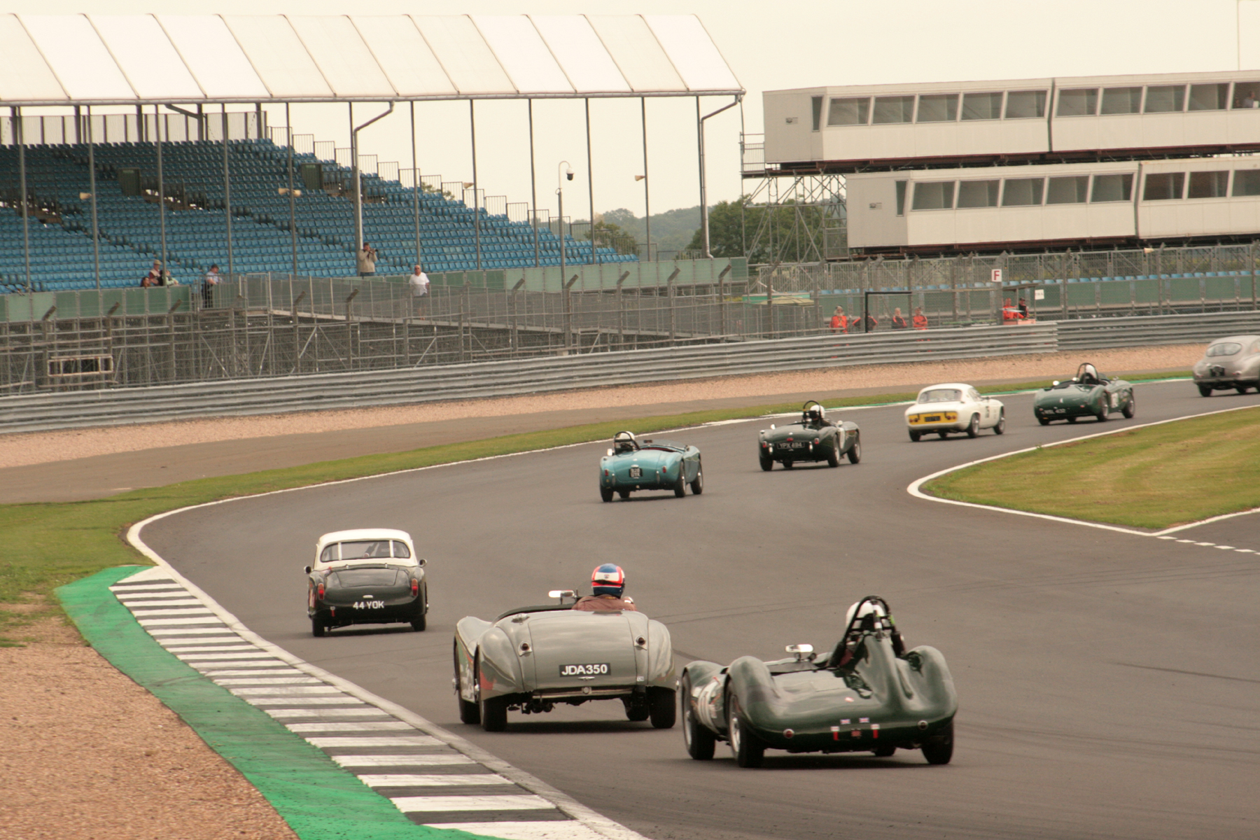 Glorious sight streaming through Woodcote - Tim Stamper with Aston DB2/4 going out of picture heads Jim Campbell, Robin Ellis, Tim Pearce, Adrian King, and now slightly detached Mark Hoble, John Harper & Alex Quattlebaum - see text above  Photo - JT