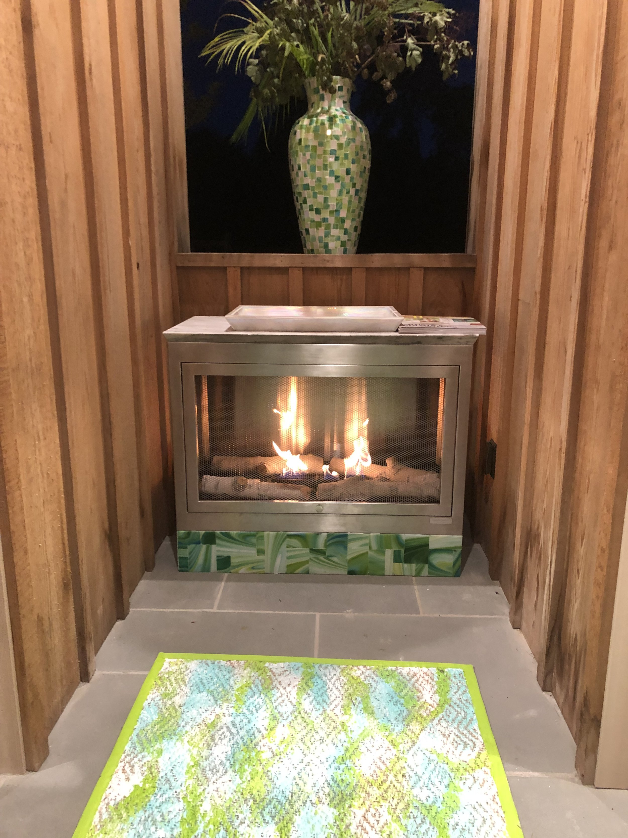 HearthCabinet's Stainless Steel three-sided outdoor unit takes center stage in the pool cabana of the Hampton House, and features a custom, handblown glass mosaic by designer, Allison Eden, in shades of green and white, accompanied by an Allison Eden hand-painted rug and mosaic vase.