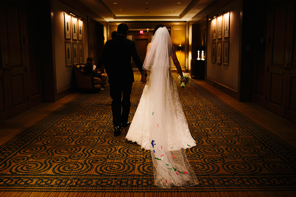 Bride and groom walk down the hall at the Four Seasons Hotel Boston.