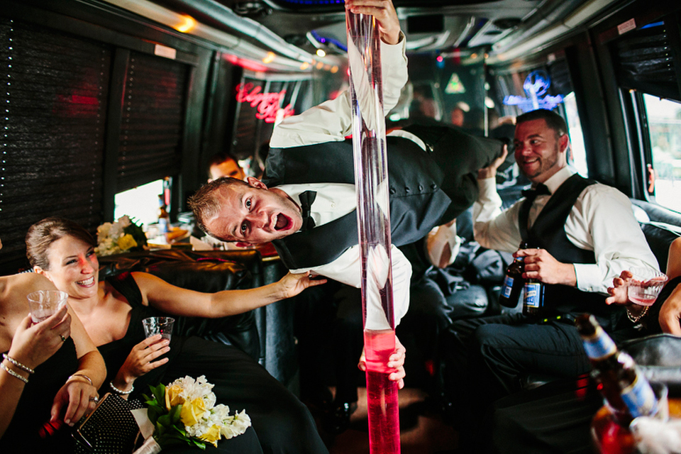 The wedding party on the party bus with groomsman on the pole.