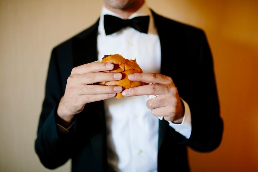 groom eating a hamburger while in tuxedo