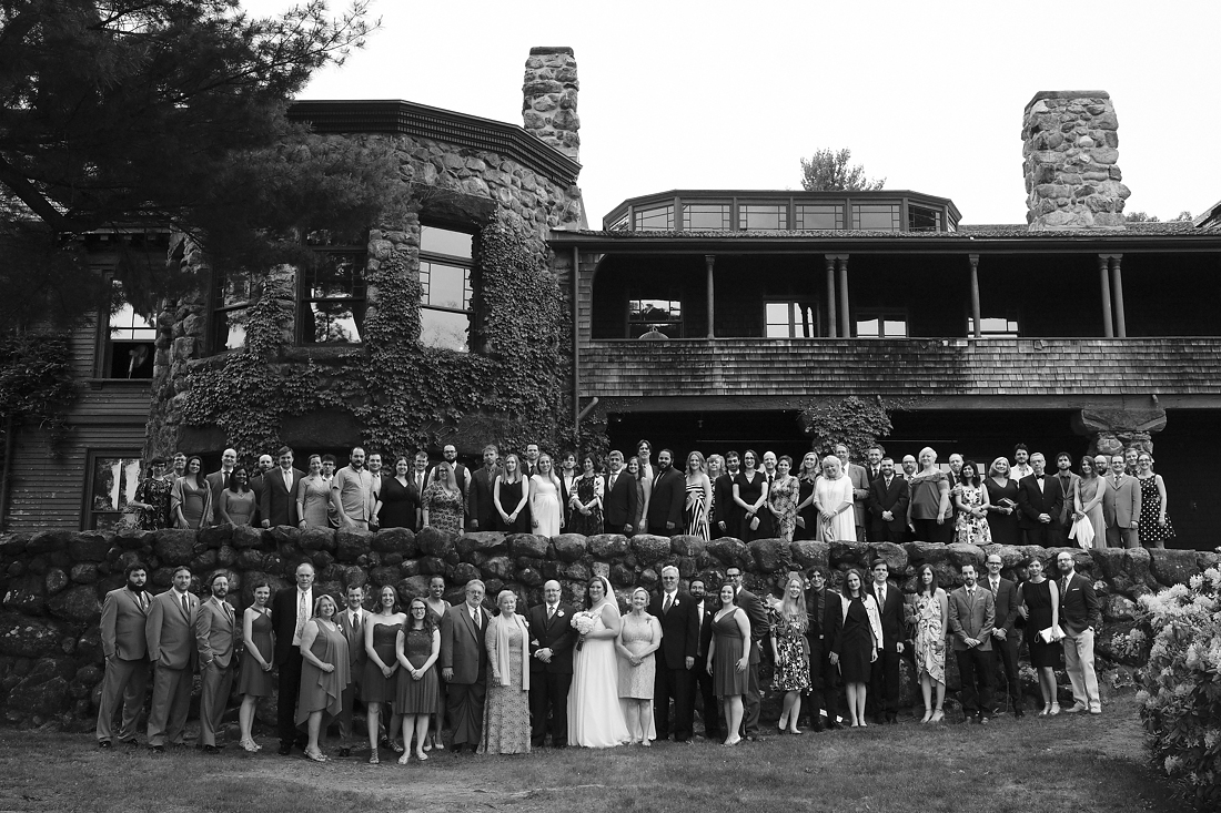 bride and groom with guests posed outside stonehurst robert treat paine estate wedding.