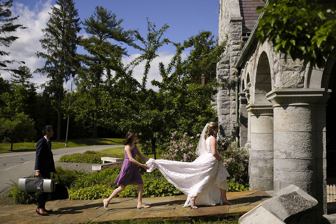 bride enters church with maid of honor at wedding in stockbridge in western massachusetts