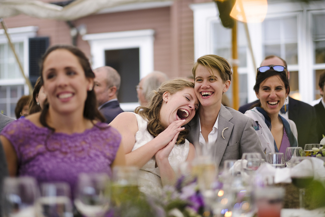 two brides laughing during speeches at their western massachusetts wedding in stockbridge