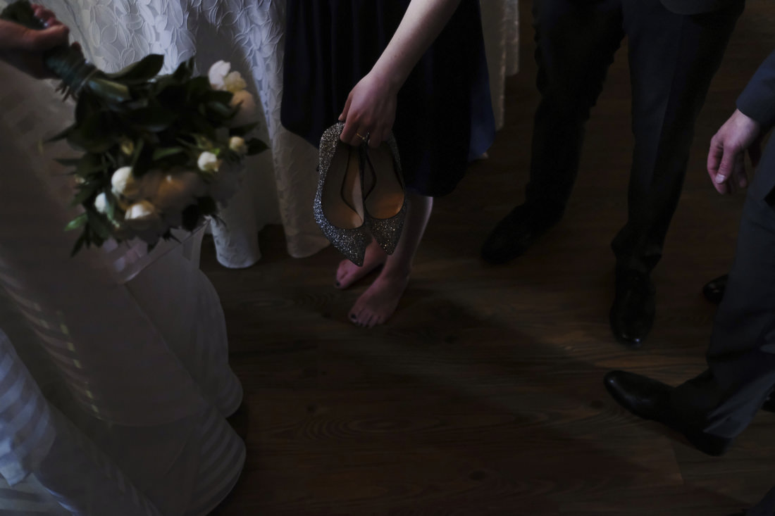 bridesmaid holds shoes next to bride at charles river museum wedding in waltham, ma