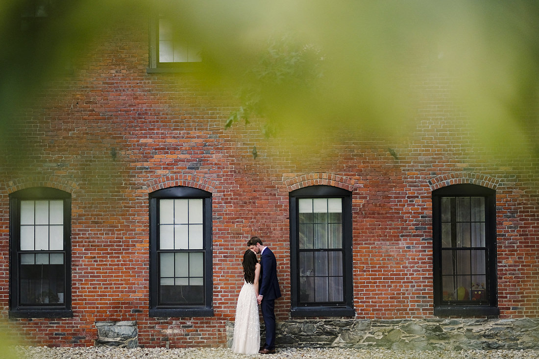 portrait of bride and groom kissing outside the charles river museum of industry and innovation