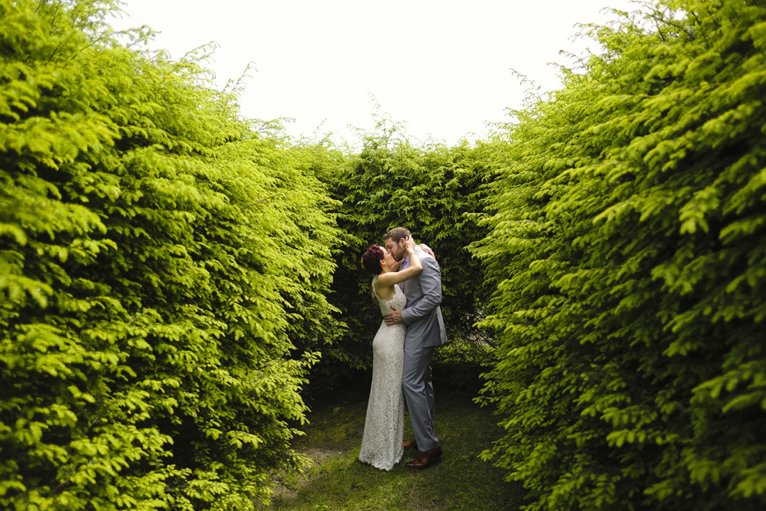 bride and groom kiss during passionate wedding portrait in labyrinth in path of life sculpture garden in vermont