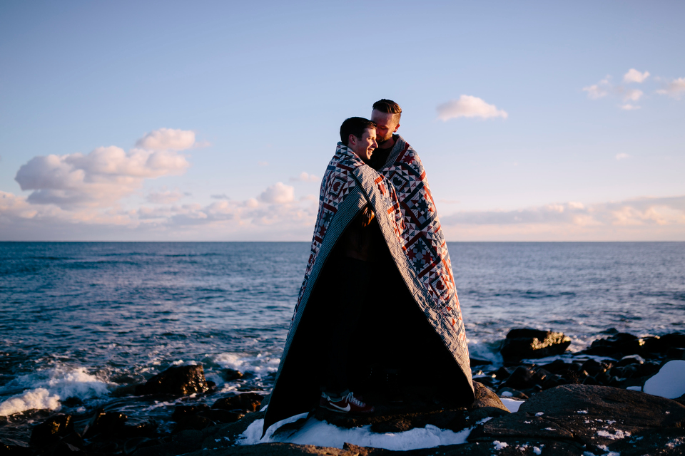 couple keeps warm under blanket at winter engagement session in portsmouth new hampshire