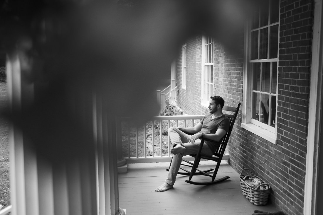 groom sits in rocking chair on porch before getting ready for his wedding at path of life sculpture garden