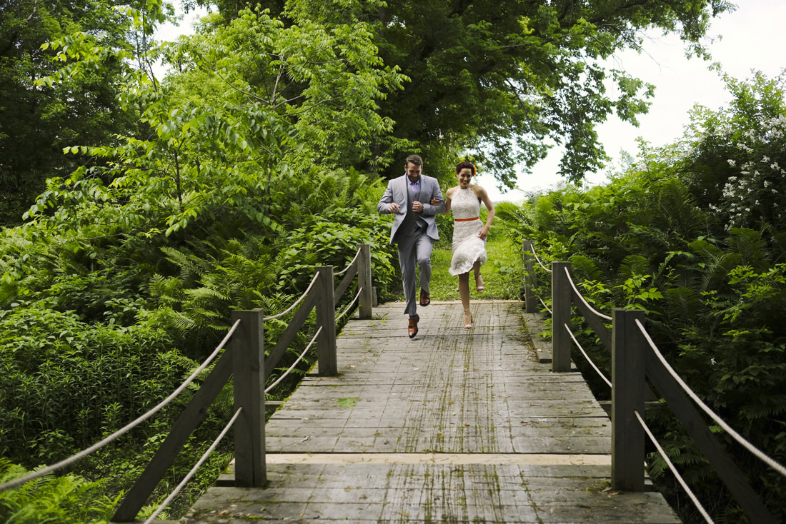 bride and groom skip across wooden bridge during portrait session at path of life sculpture garden in windsor, vermont
