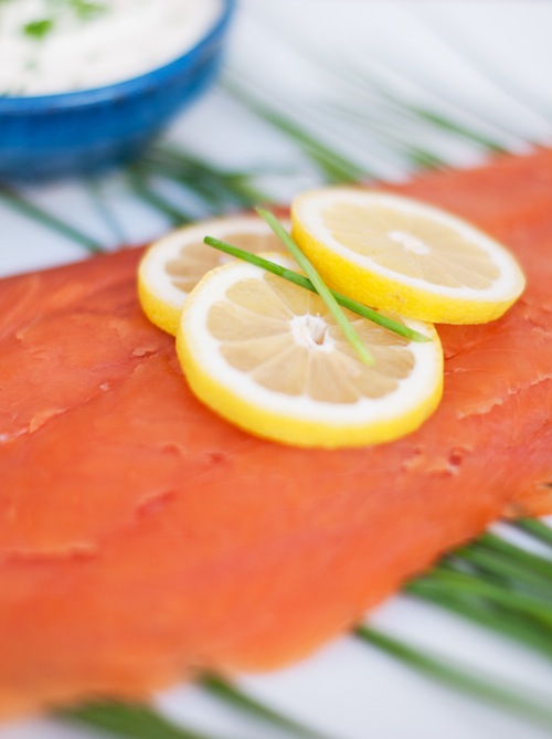 close up of sliced smoked salmon with lemon slices and chives
