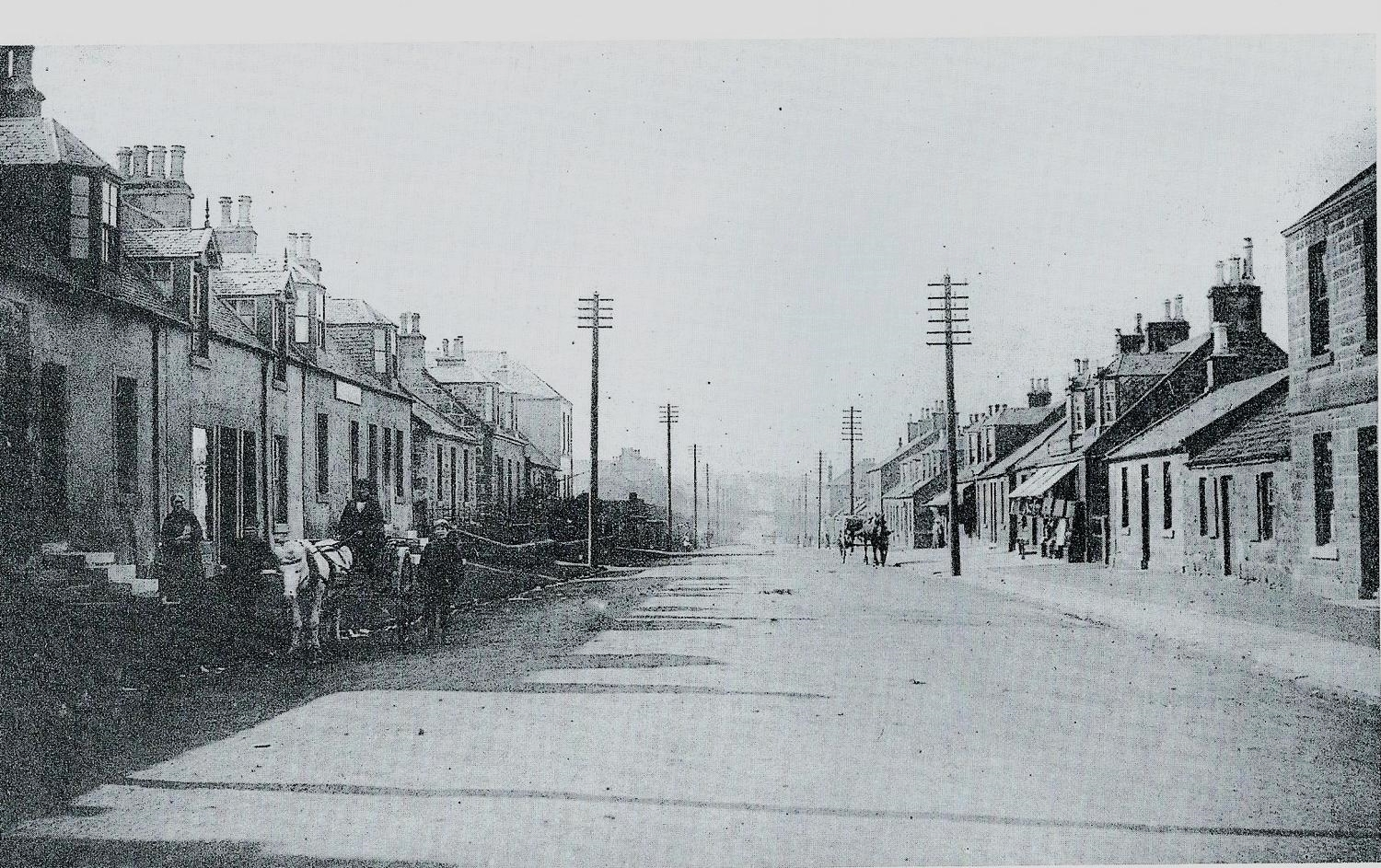 Main Street in Harthill, Lanark looking to the west. This street was for many years the main road between Edinburgh and Glasgow. Horse-drawn carts make up the traffic!